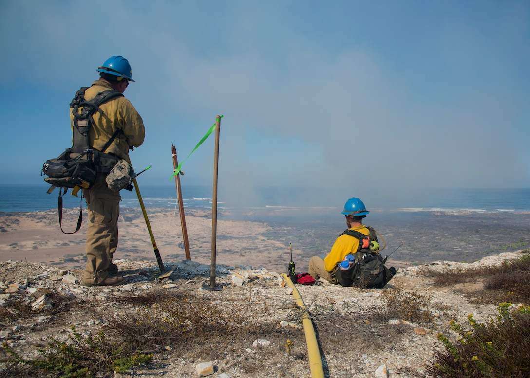 Mike Rivera and Alex Duncan, Vandenberg Wildland Support Module fire operation technicians, observe the controlled fire Sept. 18, 2019 at Vandenberg Air Force Base, Calif. The Vandenberg Fire Department and Hotshots team conducted a prescribed burn of grassland and coastal sage scrub. (U.S. Air Force photo by Airman 1st Class Aubree Milks)