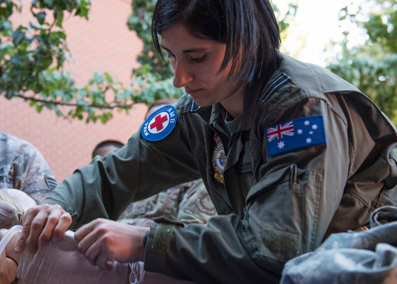 Royal Australian Air Force Flight Lt. Michelle Polgar, RAAF medic, applied a wound-dressing to a hemorrhage simulation training mannequin during the Tactical Combat Casualty Care course at Fairchild Air Force Base, Washington, Sept. 12, 2019. TCCC is designed to help lessen preventable combat deaths by providing proven trauma stabilization techniques, allowing for wounded to survive long enough to receive life-saving treatment. (U.S. Air Force photo by Senior Airman Ryan Lackey)