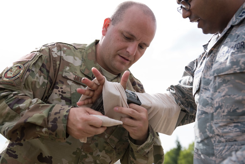 U.S. Air Force 1st Lt. Jeremy Deep, Air Mobility Command aeromedical operations officer, applies a splint to U.S. Air Force Capt. Amaro Mascarenhas, 375th Aeromedical Evacuation Squadron resource management officer, during the Tactical Combat Casualty Care course at Fairchild Air Force Base, Washington, Sept. 12, 2019. The TCCC is the replacement for the former Self-Aid Buddy Care first aid training and will become the new standard across all U.S. military service branches. (U.S. Air Force photo by Senior Airman Ryan Lackey)