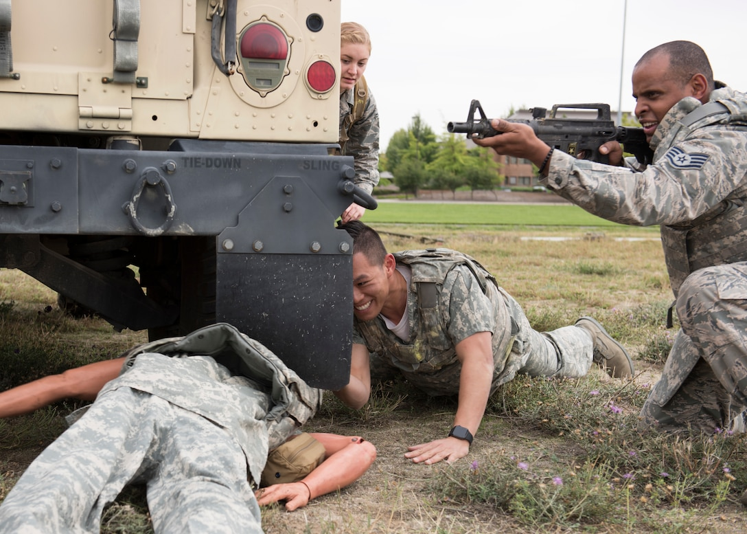 U.S. Air Force students provide cover while pulling a 'wounded' training mannequin out of simulated line-of-fire during the Tactical Combat Casualty Care course at Fairchild Air Force Base, Washington, Sept. 12, 2019. Battlefield simulation drills are vital to provide medics and combat personnel with realistic situations where they provide life-saving care and evacuation of wounded. (U.S. Air Force photo by Senior Airman Ryan Lackey)
