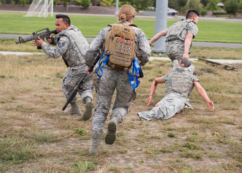 U.S. Air Force students provide cover while pulling a 'wounded' training mannequin out of the simulated line-of-fire during the Tactical Combat Casualty Care course at Fairchild Air Force Base, Washington, Sept. 12, 2019. Battlefield simulation drills are vital to provide medics and combat personnel with realistic situations where they provide life-saving care and evacuation of wounded. (U.S. Air Force photo by Senior Airman Ryan Lackey)