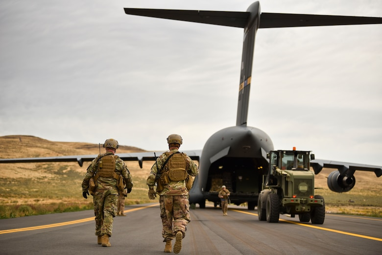 U.S. Air Force Airmen walk to a C-17 Globemaster III from Charleston Air Force Base, South Carolina, to direct Airmen where to go during the Air Mobility Command's Mobility Guardian exercise.