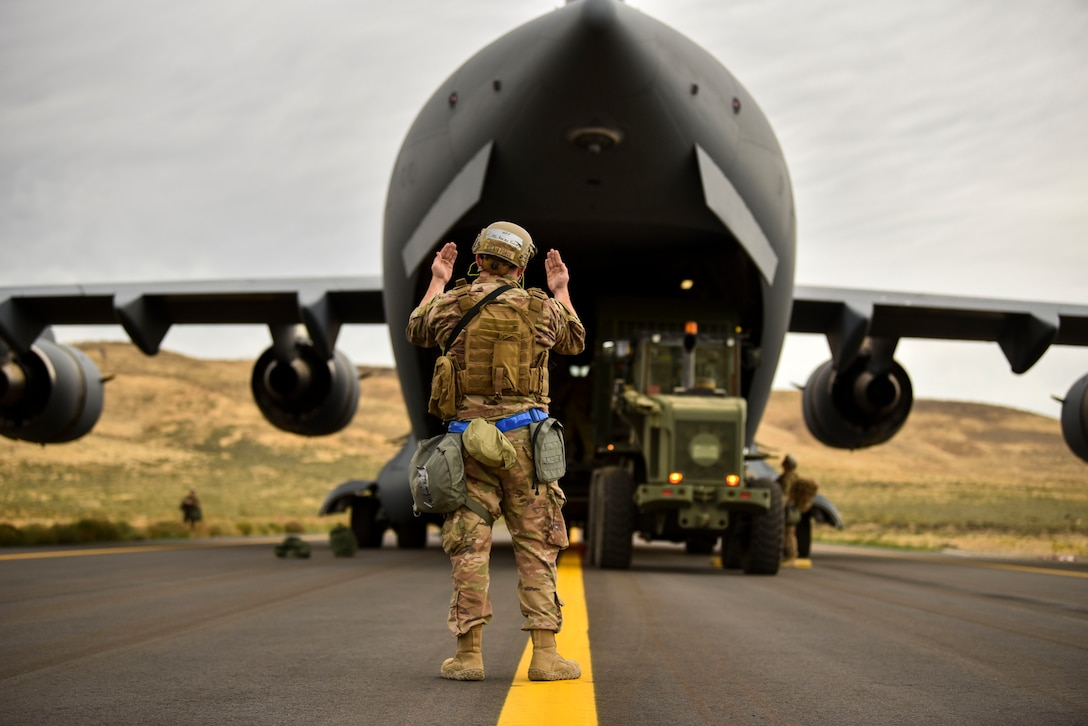 U.S. Air Force Airman 1st Class Kainon Roberts directs a forklift carrying equipment from a C-17 Globemaster III from Charleston Air Force Base, South Carolina, as part of a Joint Forcible Entry operation during Air Mobility Command's Mobility Guardian exercise.