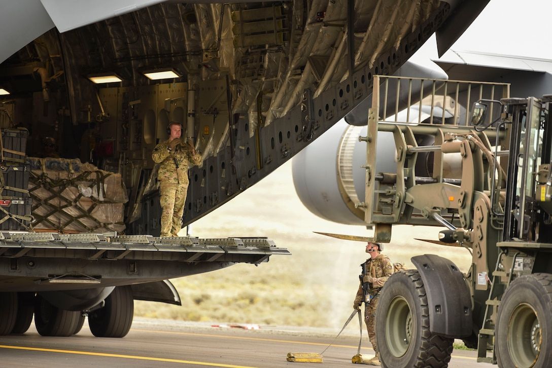 A U.S. Air Force Airman directs a forklift towards a C-17 Globemaster III to unload cargo from the C-17 as part of a Joint Forcible Entry operation during Air Mobility Command's Mobility Guardian exercise.
