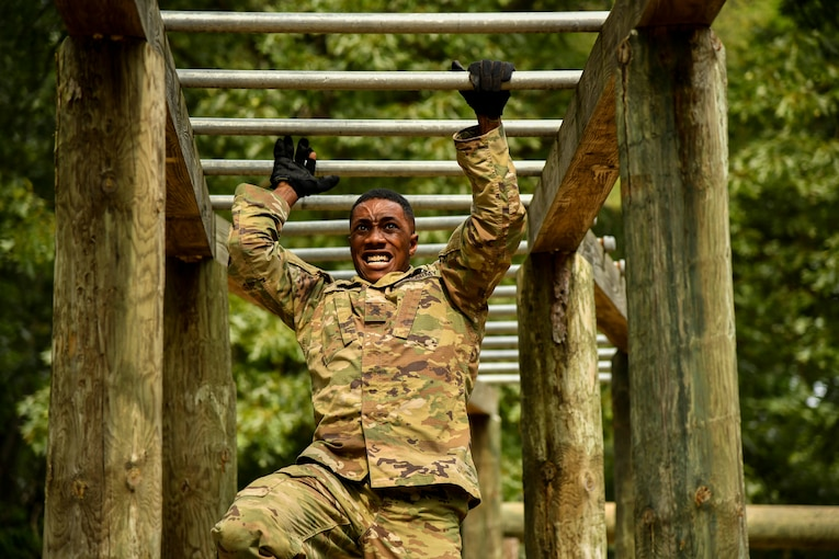 A soldier swings from one bar to the next on an obstacle.
