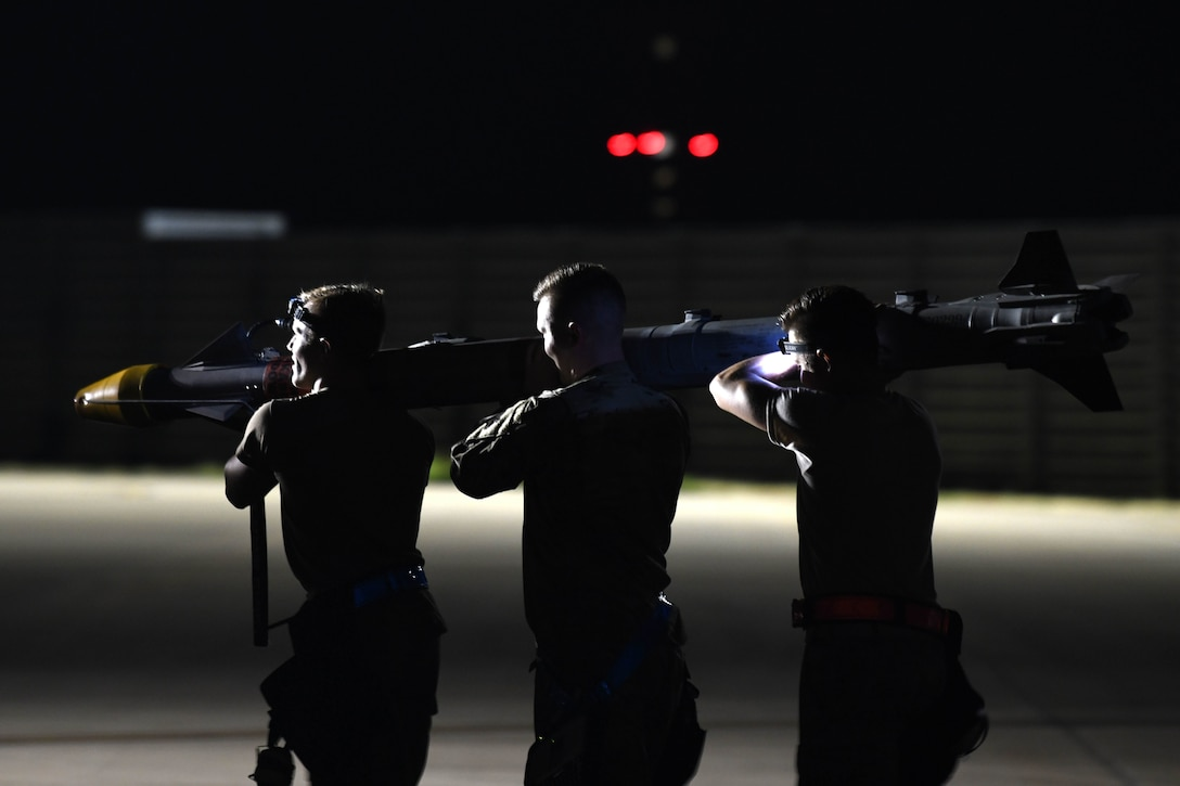 Three airmen carry a missile at night.
