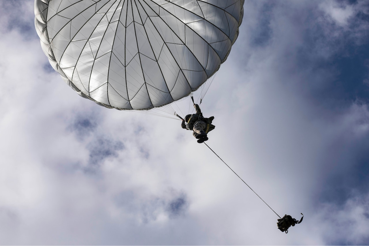 A paratrooper descends via parachute above his rucksack.
