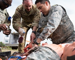 Instructors and students interact over a 'wounded' training mannequin during the Tactical Field Care phase of the Tactical Combat Casualty Care course at Fairchild Air Force Base, Washington, Sept. 12, 2019. In a continued effort to save lives, the U.S. Air Force Surgeon General has mandated that all personnel quickly become TCCC certified. (U.S. Air Force photo by Senior Airman Ryan Lackey)