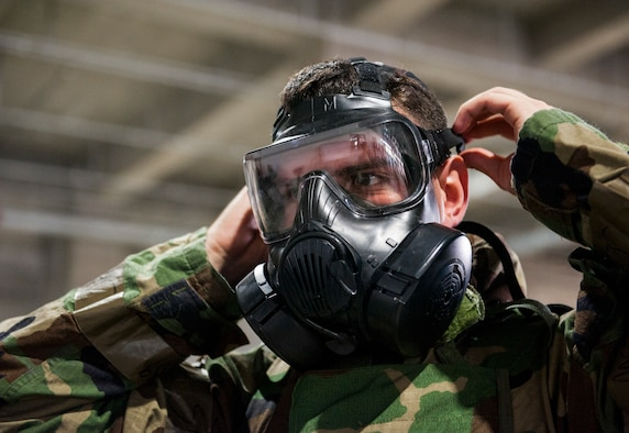An Airman tightens his M50 gas mask while putting on his Mission Oriented Protective Posture gear during Ability to Survive and Operate training at Kadena Air Base, Japan, Sept. 12, 2019. The equipment is donned in the event of a chemical, biological, radiologic or nuclear threat. (U.S. Air Force photo by Naoto Anazawa)