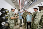A group of people tour an underground fuel storage facility.