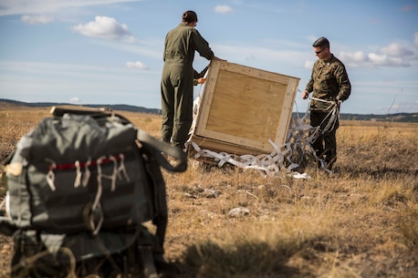 A U.S. Marine and Sailor with Special Purpose Marine Air-Ground Task Force-Crisis Response-Africa 19.2, Marine Forces Europe and Africa, recover a cargo bundle that was dropped from a U.S. Marine Corps KC-130J during a Joint Precision Air Delivery System exercise in Zaragoza, Spain, Aug. 20, 2019. The delivery system is an airdrop device that uses prepared geographic coordinates programmed into a computer system to guide the parachute to the ground. SPMAGTF-CR-AF is deployed to conduct crisis-response and theater-security operations in Africa and promote regional stability by conducting military-to-military training exercises throughout Europe and Africa. (U.S. Marine Corps photo by Cpl. Margaret Gale)