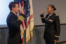 U.S. Navy Capt. Bryan Cochran administers the Oath of Office to U.S. Army Lt. Col. Tiffany Dills during her promotion ceremony at Joint Task Force Civil Support headquarters. The promotion was attended by her family, including her husband U.S. Army Lt. Col. John Dills, who is currently deployed and was able to attend via video teleconference.  (Official DoD photo by Mass Communication Specialist 3rd Class Michael Redd/RELEASED)