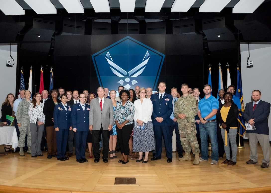 About 50 Air Force members pose for a group photo on a stage.