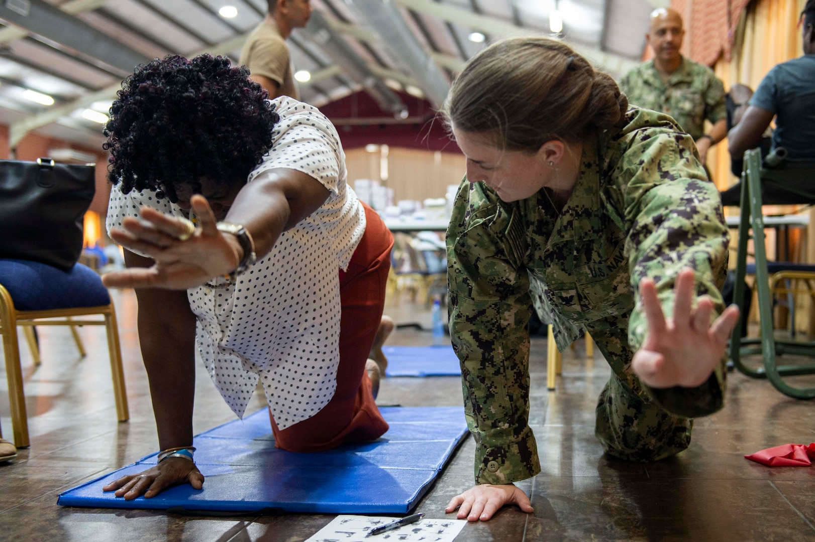 A physical therapist teaches stretching exercises to a Grenadian woman