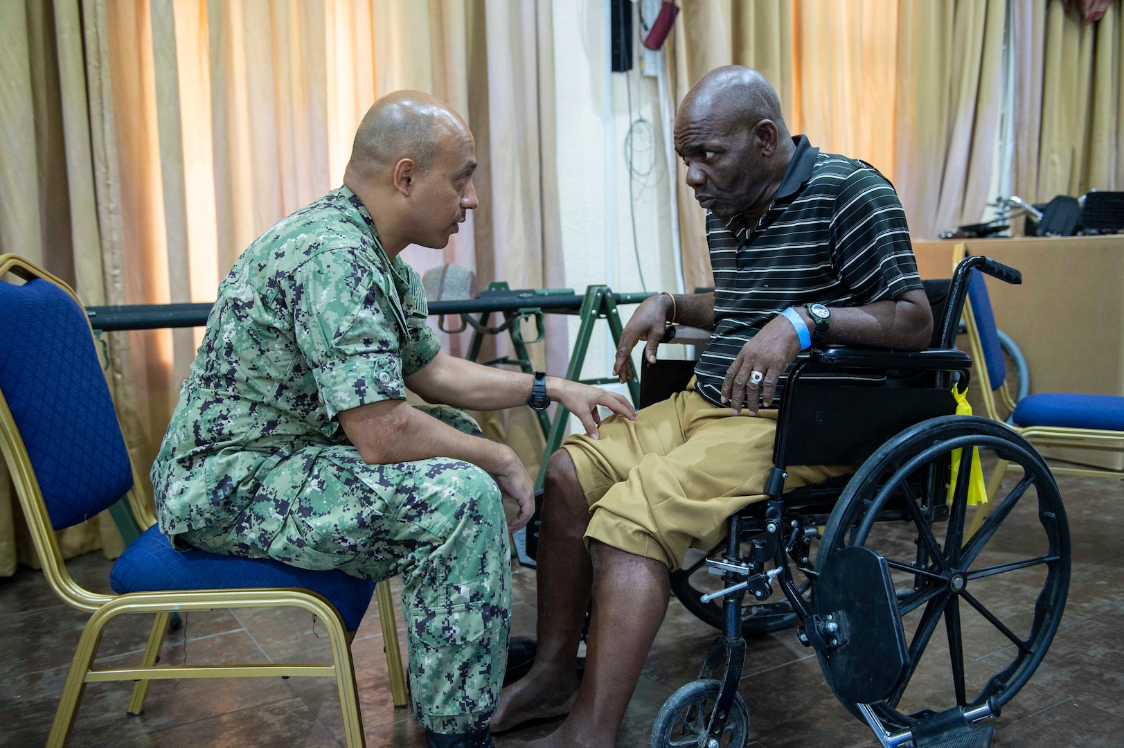 A physical therapist examines a Grenadian man's legs