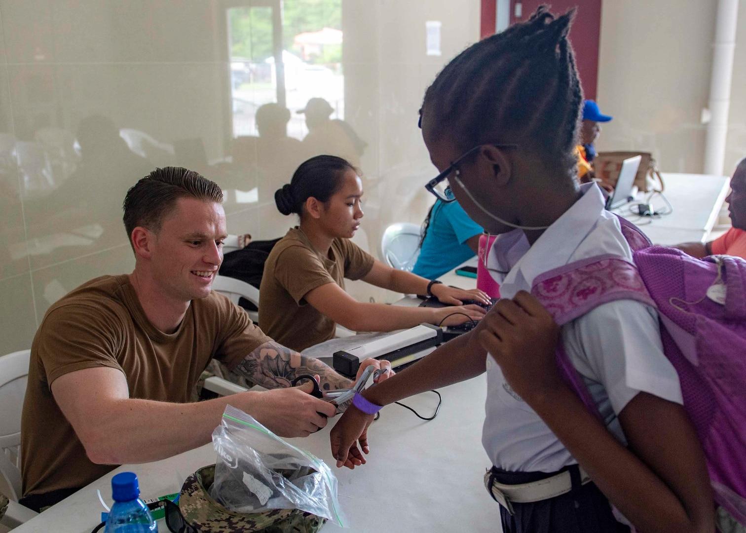 A Sailor removes a Grenadian girl's bracelet.