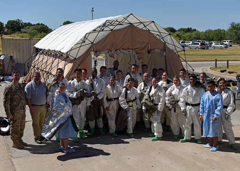 Personnel from the 17th Medical Group stand outside of the decontamination center during their medical in-place decontamination training at the Ross Clinic on Goodfellow Air Force Base, Texas, September 12, 2019. This training is to prepare medical personnel to handle decontaminations in emergency situations. (U.S. Air Force photo by Airman 1st Class Robyn Hunsinger/Released)