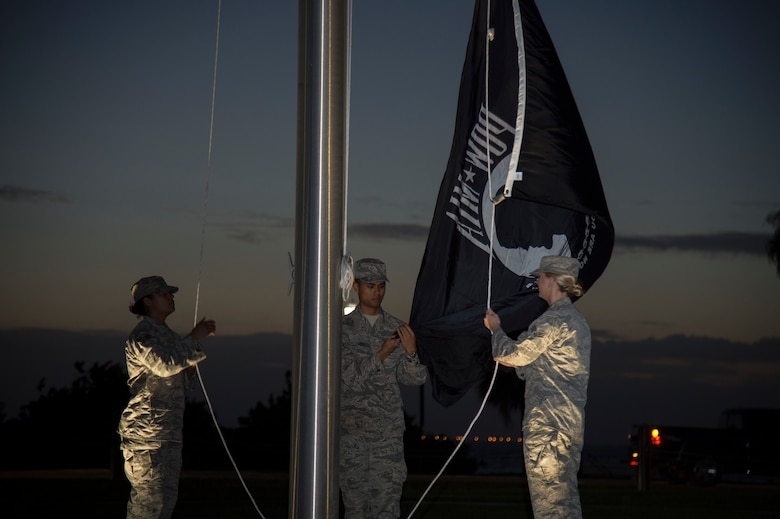 U.S. Air Force Senior Airman Karina Rodriguez (left), Airman 1st Class Dyllan Hipol (center), and Senior Airman Andrea Stutts (right), MacDill Air Force Base honor guardsmen, raise the POW/ MIA Flag Sept. 20, 2019, at MacDill AFB, Fla.  POW/MIA Recognition Day is commemorated nationally on the third Friday of every September in honor of service members who were prisoners of war as well as those are missing in action. (U.S. Air Force photo by Airman 1st Class Shannon Bowman)