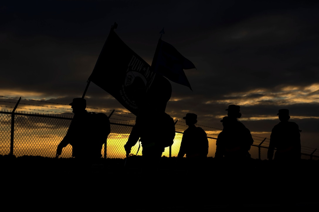 Several service members walk at sunrise carrying two flags.
