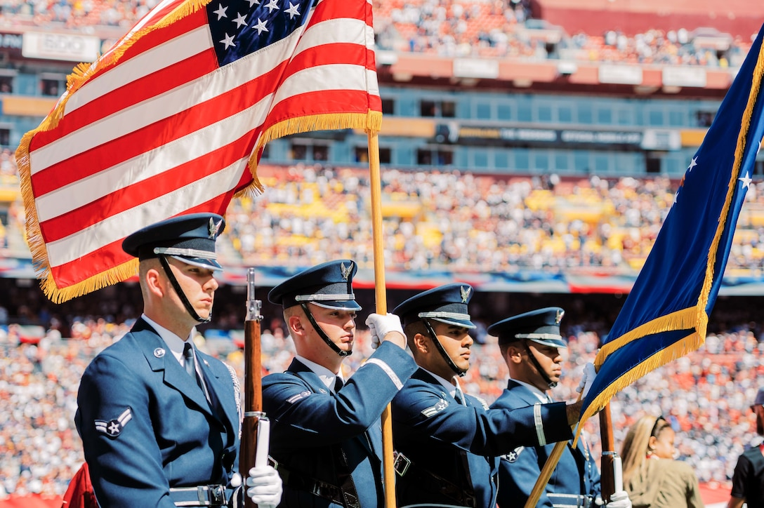 The United States Air Force Honor Guard presents the colors at a football game