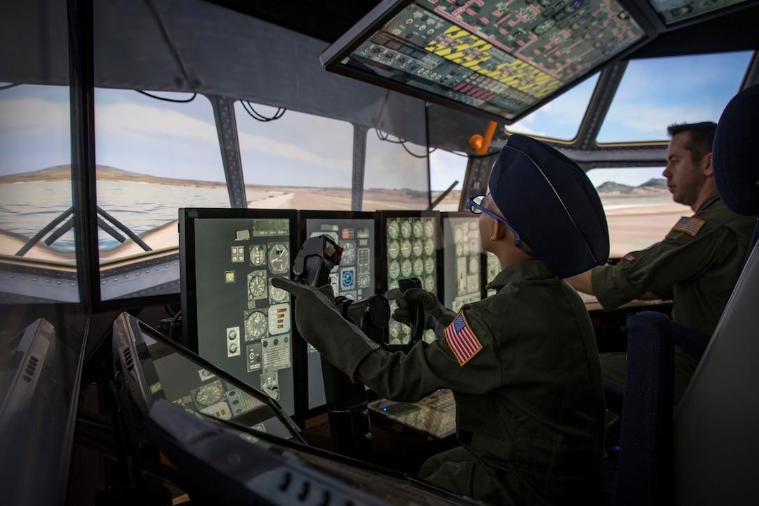 Ayden Houston and Maj. Richard Stocker fly a C-130 Hercules flight simulator