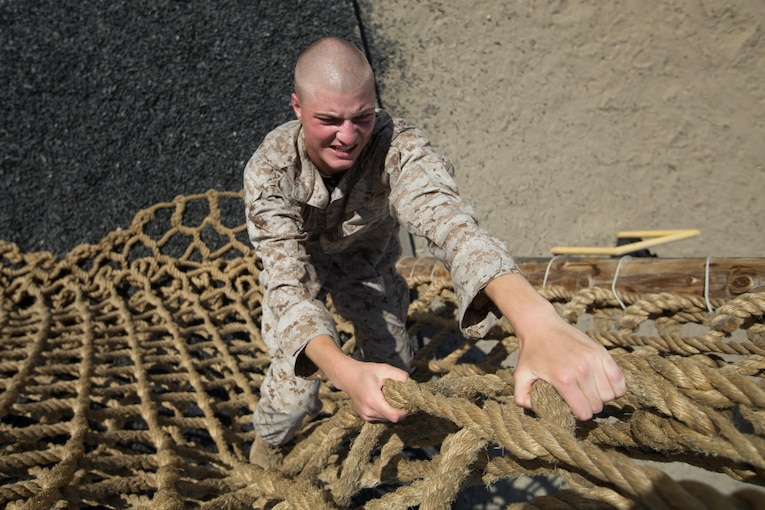 A Marine Corps recruit grimaces as he climbs up a cargo net.
