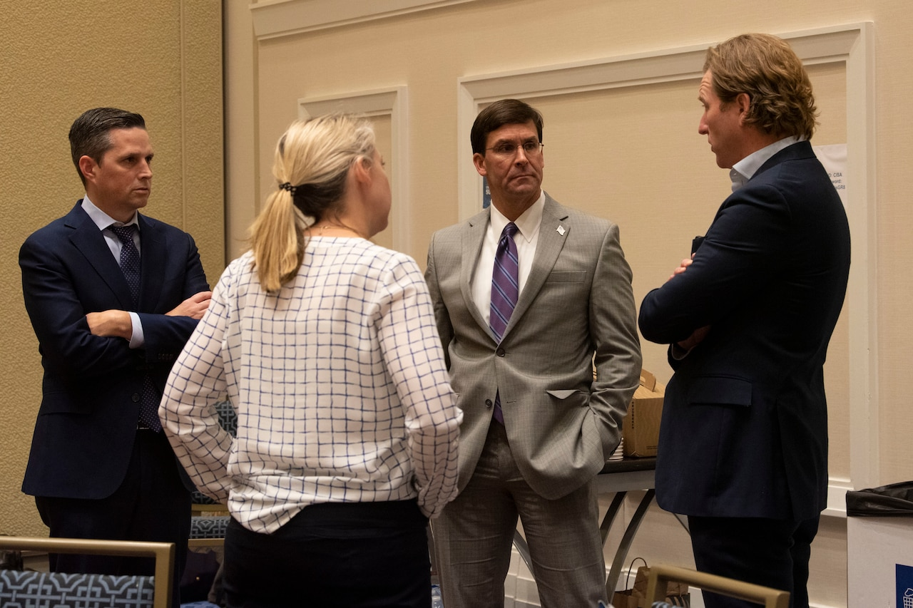 Three men in suits and a woman stand in a circle talking.