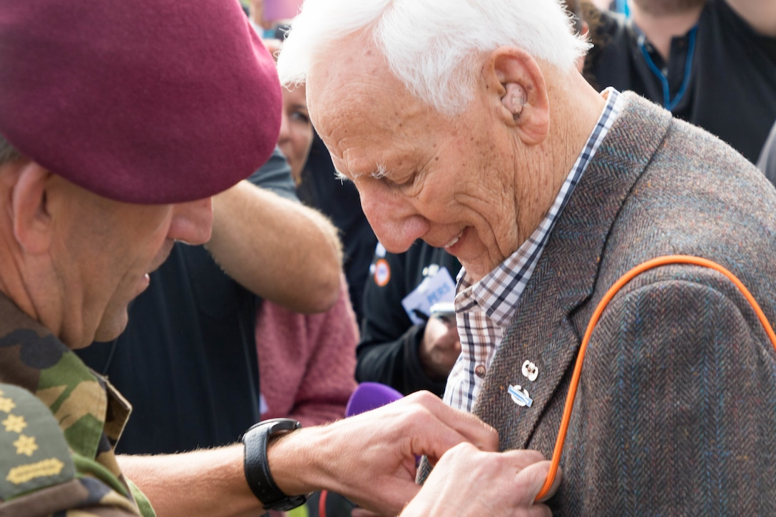 Dutch army officer attaches lanyard to World War II veteran's shoulder.