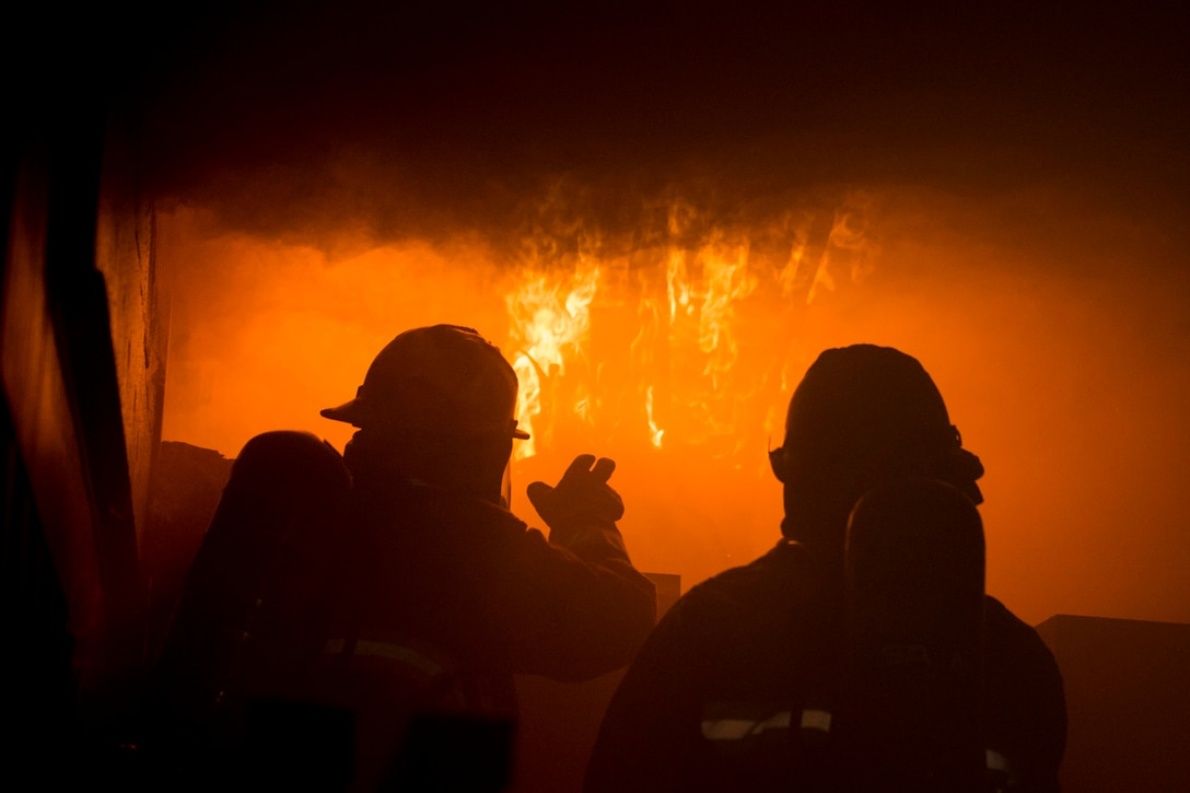 Two airmen face a large fire.