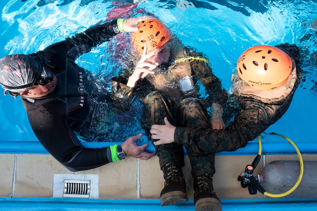 A Marine is held by two other men as he comes up for air in a swimming area.