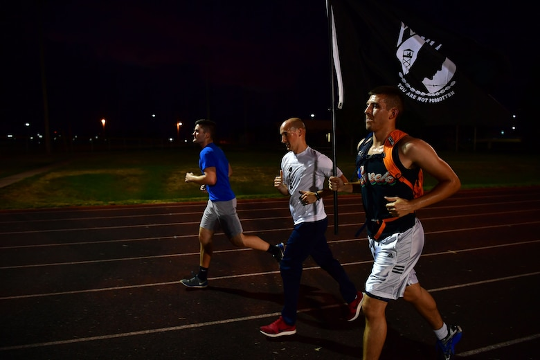 Airman run at night with POW/MIA flag.
