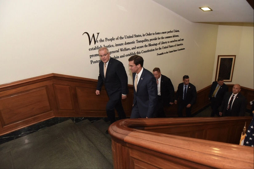 Men in suits walk up a staircase that has text from the preamble of the U.S. Constitution printed on one wall.