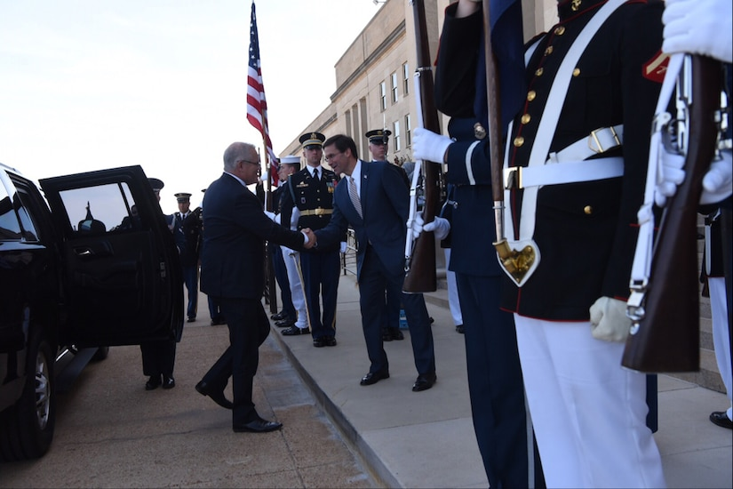 Men in suits shake hands while flanked by service members in dress uniforms.