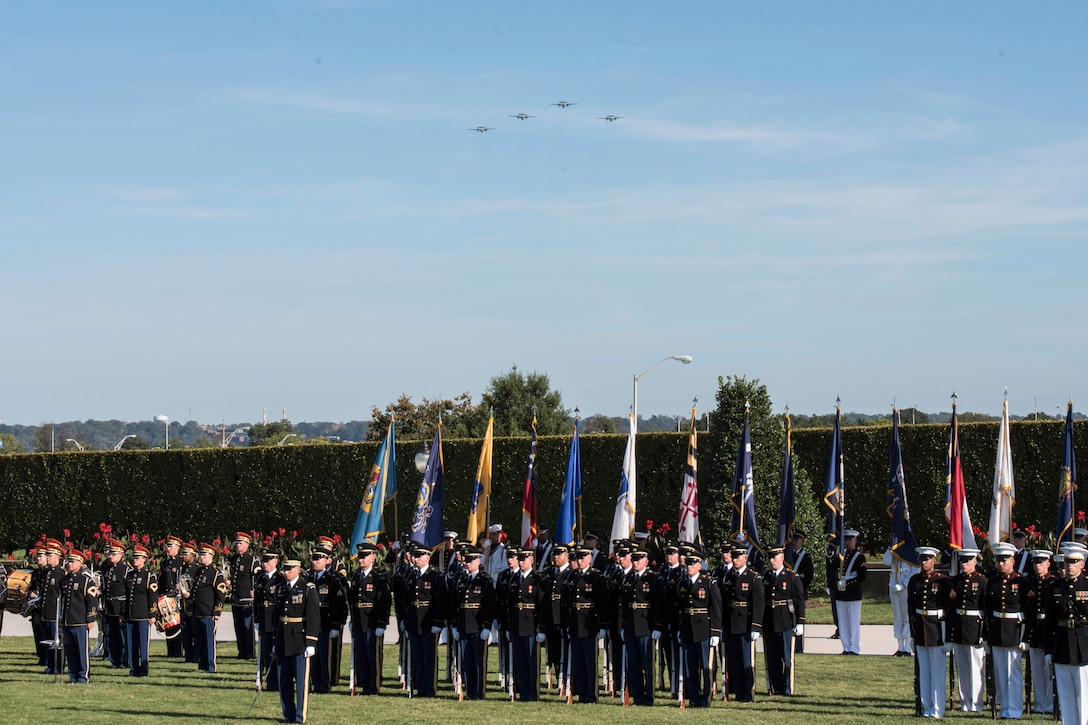 Planes in a missing man formation fly over joint service honor guard members on a lawn.