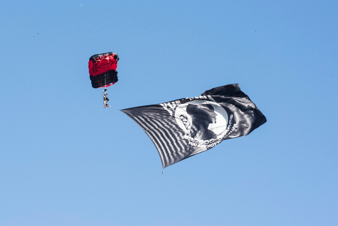 A service member descends through the air with a parachute and a flag,