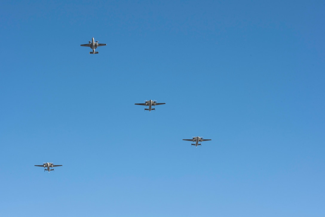 A group of aircraft perform the missing man formation,