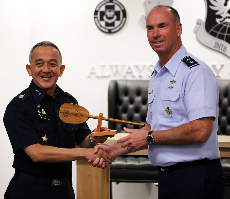 U.S. Air Force Maj. Gen. Brian Killough, Pacific Air Forces deputy commander, presents Air Marshal Tarin Punsri, Royal Thai air force, a gift from Hawaii during the closing ceremonies of the sixth Airman-to-Airman talks at Camp Murray, Wash., Aug. 28, 2019. A2A talks are jointly held conferences between PACAF and regional partner air forces designed to bring together both air forces to discuss and improve on training, tactics and procedures. This year marked the first talks to include participation by the Washington National Guard, with Washington state as the state partner to Thailand since 2002. (U.S. National Guard photo by Joseph Siemandel)
