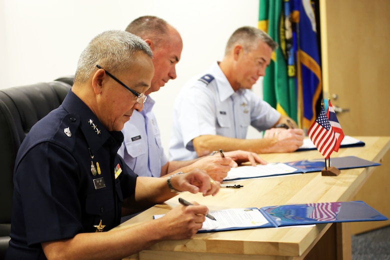 Air Marshal Tarin Punsri, Royal Thai air force, U.S. Air Force Maj. Gen. Brian Killough, Pacific Air Forces deputy commander and Brig. Gen. Jeremy Horn, Washington Air National Guard commander, sign an agreement between units after the sixth Airman-to-Airman talks at Camp Murray, Wash., Aug. 28, 2019. A2A talks are jointly held conferences between PACAF and regional partner air forces designed to bring together both air forces to discuss and improve on training, tactics and procedures. This year marked the first talks to include participation by the Washington National Guard, with Washington state as the state partner to Thailand since 2002. (U.S. National Guard photo by Joseph Siemandel)