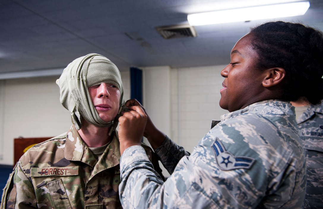 An Airman practices bandaging during Ability to Survive and Operate training at Kadena Air Base, Japan, Sept. 12, 2019. The ATSO training tested Airmen with various emergency situations including chemical attacks, unexploded ordnance and Self-Aid and Buddy Care. (U.S. Air Force photo by Naoto Anazawa)