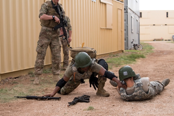 A medical technician reaches to help his fallen comrade during a scenario at the 2019 Medical Rodeo at Melrose Air Force Range, N.M., Sept. 19, 2019. The Medic Rodeo is designed to test the skills of air force medical technicians in both deployed and home installation environments. (U.S. Air Force photo by Staff Sgt. Michael Washburn)