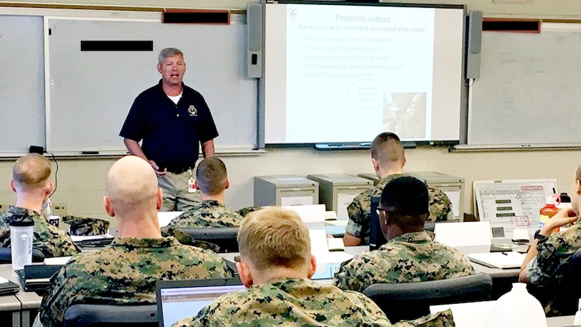 Classroom setting with instructor at the front and Marines seated in front of computers.