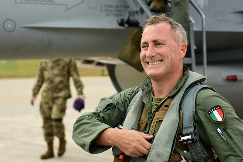 Italian air force Col. Vincenzo Tozzi, Aviano base commander, greets friends and family after exiting an F-16 Fighting Falcon at Aviano Air Base, Italy, Sept. 17, 2019. Col. Tozzi was given a flight in an F-16 as a show of gratitude from the 31st Fighter Wing for his time as base commander. (U.S. Air Force photo by Staff Sgt. Kelsey Tucker)