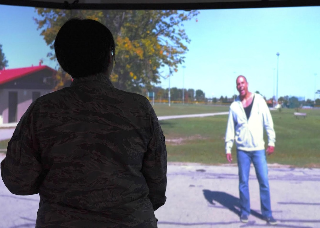 An Airman stands infront of a screen during a noise complaint simulation and tries to calm a male that is yelling.