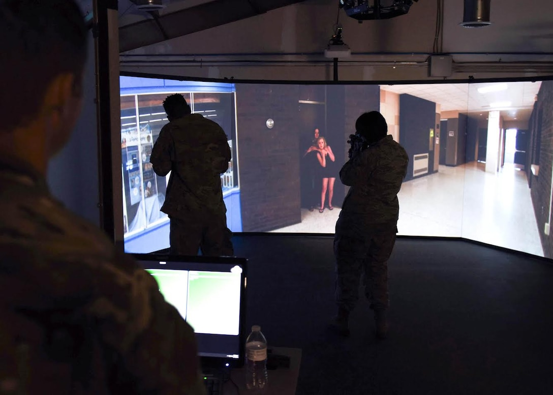 An Airman instructor watches two Airmen point inert firearms at a screen during an active school shooter simulation which shows a shooter holding a gun to a teenager's head.