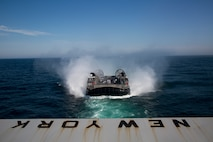 U.S. Sailors, assigned to Assault Craft Unit 4, pilot the Landing Craft, Air Cushion (LCAC) as it approaches the San Antonio-Class amphibious transport dock ship USS New York (LPD 21) for training operations during the Bataan Amphibious Ready Group (ARG), Marine Expeditionary Unit (MEU) exercise (ARGMEUEX) on Aug. 23, 2019, off the coast of Virginia. The Bataan ARG and 26th MEU are enhancing joint integration, lethality and collective capabilities of the Navy-Marine Corps team through joint planning and execution of challenging and realistic training scenarios. (U.S. Marine Corps photo by Staff Sgt. Patricia A. Morris)