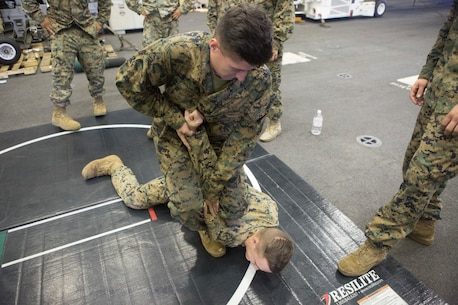 U.S. Marines with Headquarters and Support Company, Battalion Landing Team, 2nd Battalion, 8th Marine Regiment, 26th Marine Expeditionary Unit (MEU), perform a martial arts movement as part of a class on the Marine Corps Martial Arts Program (MCMAP) aboard the amphibious assault ship USS Bataan (LHD 5) during Amphibious Ready Group (ARG), MEU exercise (ARGMEUEX) in the vicinity of Camp Lejeune, North Carolina, Aug. 26, 2019. MCMAP is a combat system developed by the United States Marine Corps to combine hand-to-hand, close-quarters combat techniques with morale, team-building functions and instruction in the Warrior Ethos. (U.S. Marine Corps photo by Staff Sgt. Pablo Morrison)