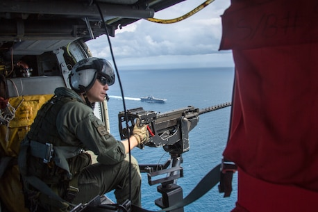 U.S. Navy Air Crewman 2nd Class Berk Tarleton, an MH-60 Seahawk crew chief with Amphibious Squadron (PHIBRON) 8, mans a .50-caliber machine gun during a simulated strait transit as part of Amphibious Ready Group (ARG), Marine Expeditionary Unit (MEU) exercise (ARGMEUEX) in the vicinity of South Carolina, Aug. 30, 2019. Rehearsing strait transits help make the ARG/MEU team a more versatile, sea-based expeditionary force that can be tailored to a variety of missions. (U.S. Marine Corps photo by Cpl. Nathan Reyes)