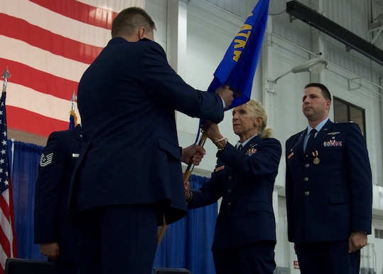 Lt. Col. Roxellen Auletto (middle) receives the 174th Medical Group's guidon from Col. Michael R. Smith (left), 174th ATKW Commander, during a change of command ceremony held at Hancock Field Air National Guard Base, September 7. (U.S. Air National Guard photo by Staff Sgt. Duane Morgan)
