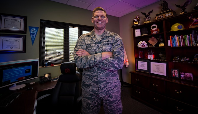 An Airman stands in the middle of his office and smiles for a photo.