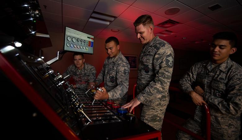 Four Airmen use a fire engine simulator for training.